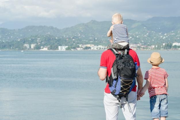 Vader met twee zonen staat op het strand. uitzicht vanaf de achterkant
