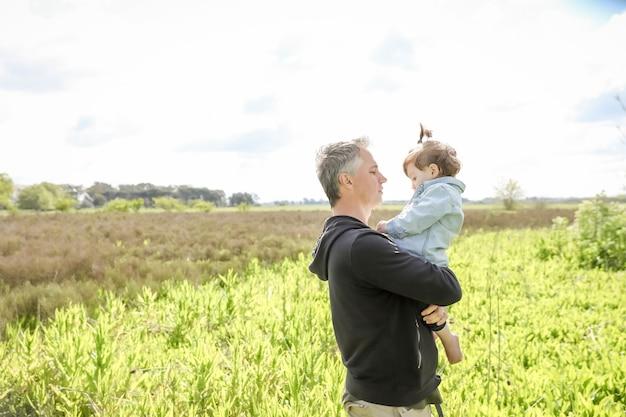 Vader met zijn dochtertje in zijn armen in het veld