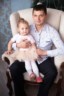Vader met zijn dochtertje zit in een leunstoel