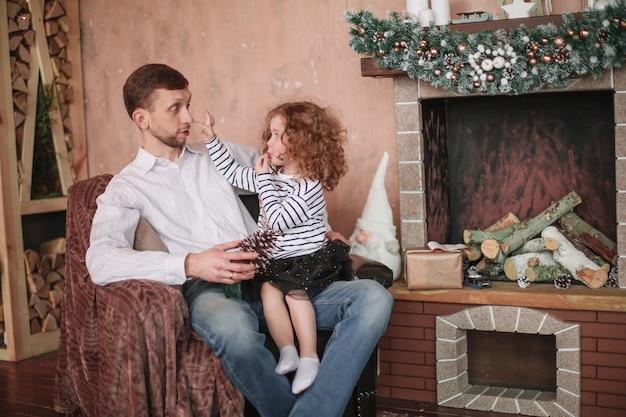 Vader met zijn dochtertje zittend in een gezellige woonkamer.