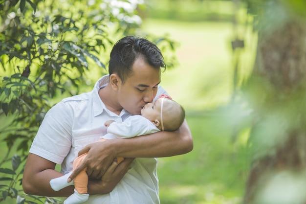 Vader met zijn pasgeboren baby in park.