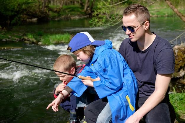 Vader met zijn zonen die op de bergrivier vissen
