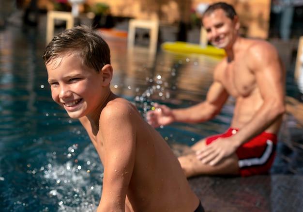 Vader met zijn zoon bij het zwembad Gratis Foto