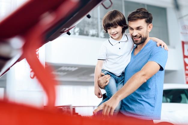 Vader met zijn zoon in zijn armen in de cabine van nieuwe auto's.