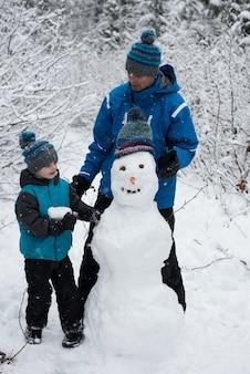 Vader met zoon die sneeuwman maakt