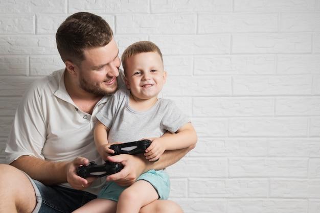 Vader met zoon het spelen met bedieningshendelclose-up