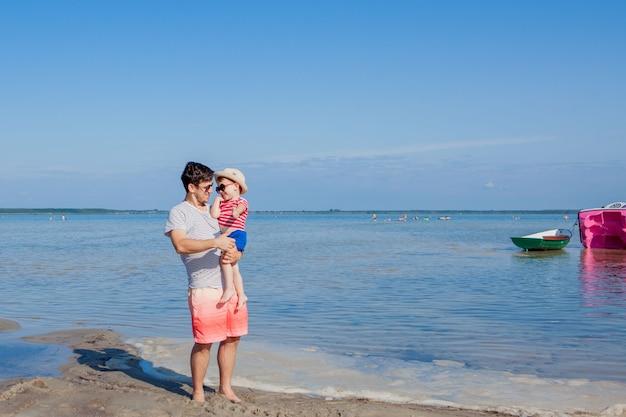 Vader met zoon op zijn handen op het strand.