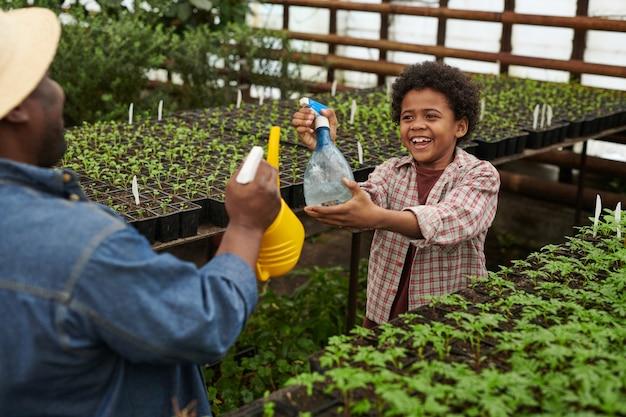 Vader met zoon plezier in de tuin, ze sproeien water op elkaar
