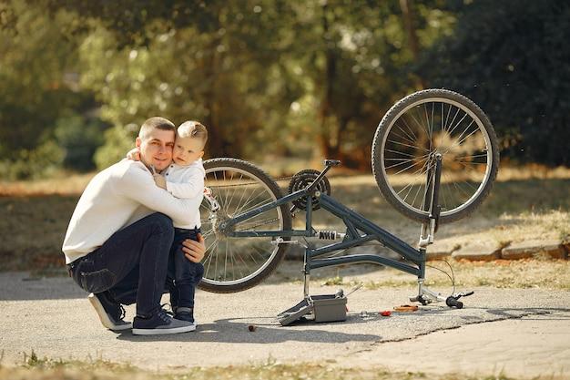 Vader met zoon repareren de fiets in een park