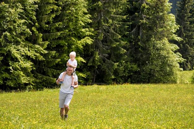 Vader met zoontje op schouders lopen op een groene weide