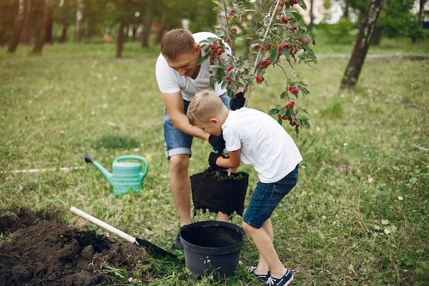 Vader met zoontje plant een boom op een erf