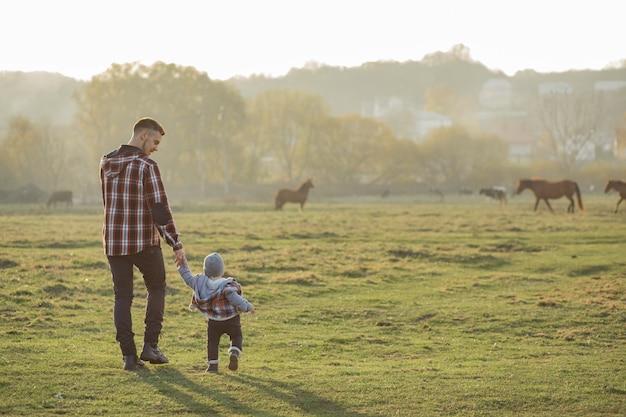 Vader met zoontje wandelen in een ochtend veld