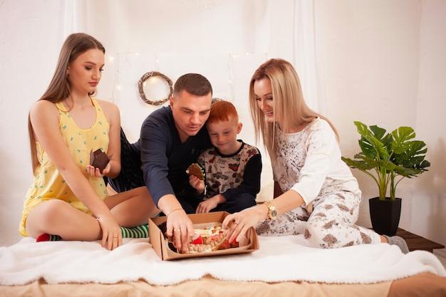 Vader, moeder, dochter en zoon eten heerlijke taarten en snoep in hun slaapkamer