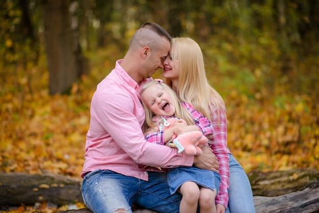 Vader moeder en dochter knuffel en zitten op een logboek tegen de achtergrond van een herfst park.