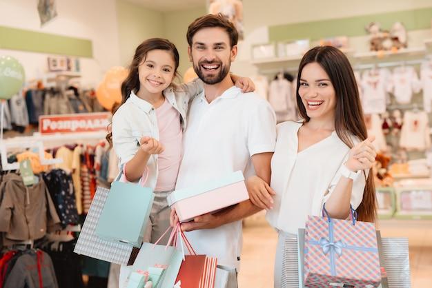 Vader, moeder en dochter zijn in kledingwinkel