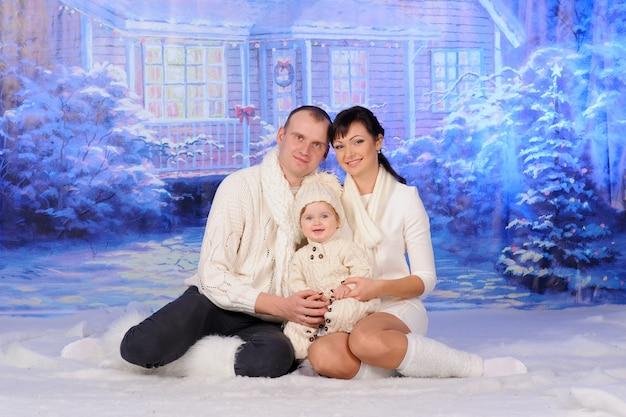 Vader moeder en dochter zitten in de sneeuw.