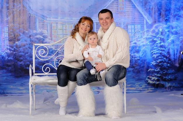 Vader moeder en dochter zitten op een bankje bij het huis.
