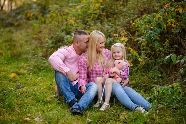 Vader moeder en dochter zitten op het gras.