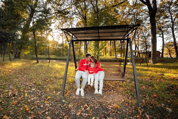 Vader, moeder en dochtertje zittend op een houten schommel in het herfstpark