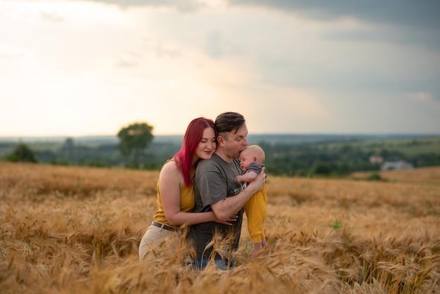 Vader, moeder en hun zoontje vermaken zich samen in een tarweveld