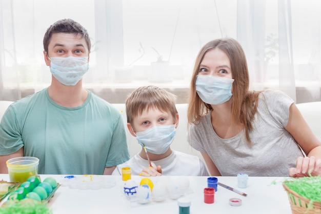 Vader, moeder en kind aan tafel in medische maskers schilderen paaseieren voor de vakantie