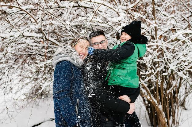 Vader, moeder en kinderen jongen hebben plezier en spelen op besneeuwde winterwandeling in de natuur.