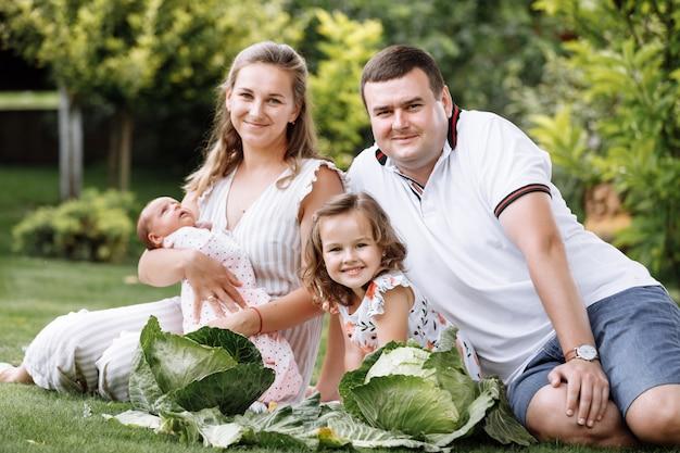 Vader, moeder en twee kinderen, babymeisje en dochtertje op het gras met kool