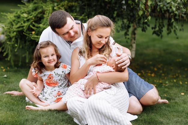 Vader, moeder en twee kinderen, babymeisje en dochtertje op het gras op zomerdag