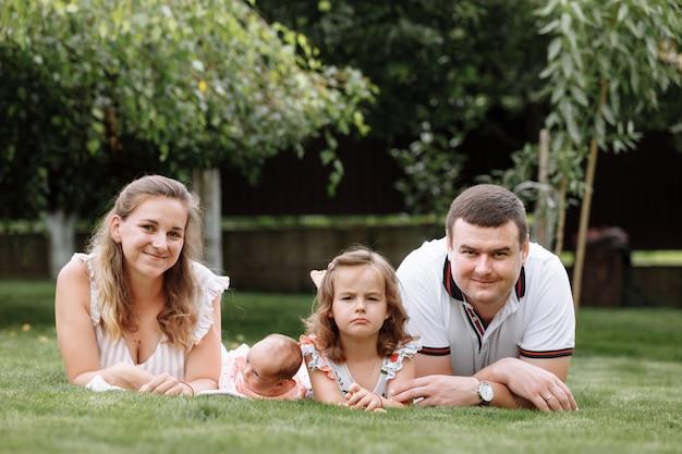 Vader, moeder en twee kinderen, babymeisje en dochtertje op het gras op zomerdag.
