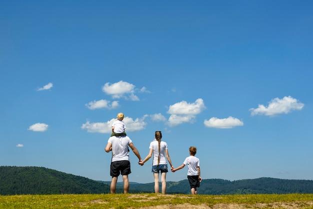 Vader, moeder en twee zoontjes staan op een groen veld op een achtergrond