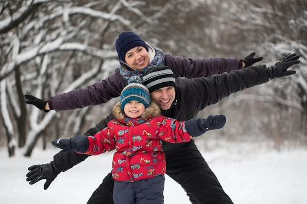Vader, moeder en zoon spelen met sneeuwballen in de winter