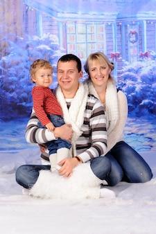 Vader moeder en zoon zitten in de sneeuw bij het huis.
