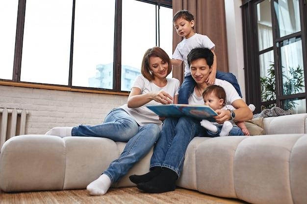 Vader, moeder, zoon en dochtertje poseren thuis