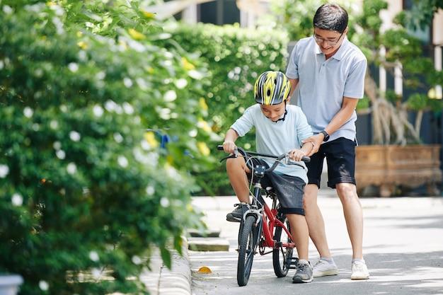 Vader ondersteunt preteen zoon in helm rijden fiets voor de eerste keer