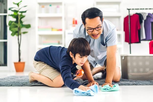Vader onderwijs aziatische jongen kleine jongen zoon gebruik desinfecterende spray fles schoonmaken en wassen vloer stof met vodden afvegen tijdens het huis samen thuis schoonmaken