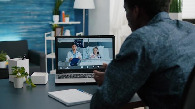 Vader op online videogesprek via laptop in gesprek met arts van ziekenhuisafdeling over gebruik van kindergez...