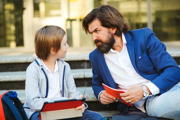 Vader praat met zoon na lessen buiten school. schooljongen met rugzak en notitieboekjes.