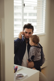 Vader praat op mobiele telefoon terwijl hij zijn baby vasthoudt