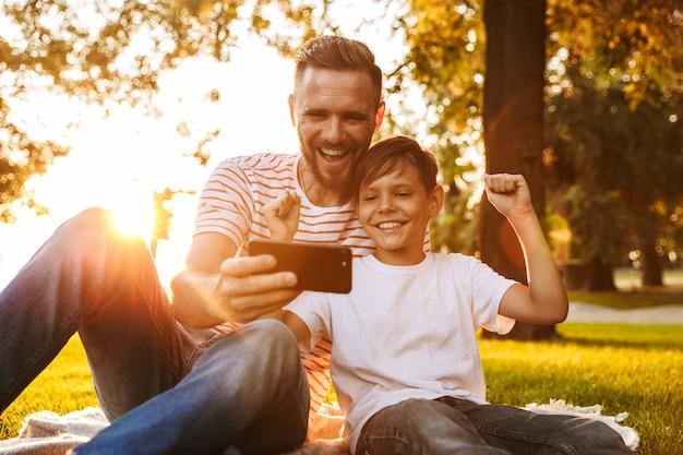 Vader rust uit met zijn zoon buiten in het park, spelletjes spelen met de mobiele telefoon.
