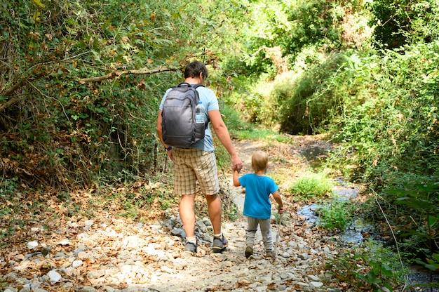 Vader samen zijn zoontje en familie tijdens een wandeling door een bergkloof overwint obstakels. vakantie in het nieuwe normaal.