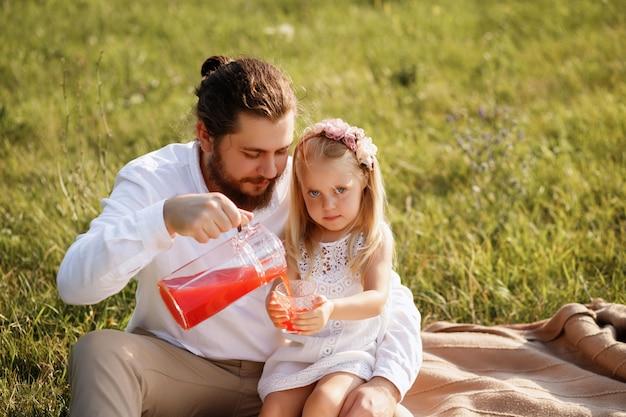 Vader schenkt sap aan dochter zomerpicknick