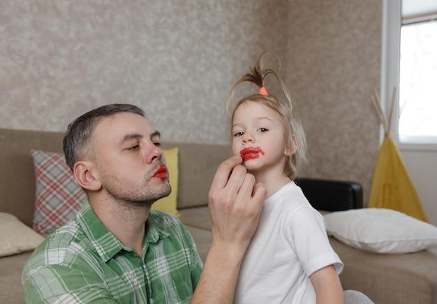 Vader schildert de lippen van zijn dochtertje met felle lippenstift