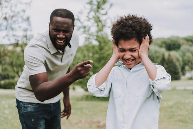 Vader scolds zoon die zich afwendt met afsluitende oren.