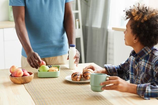 Vader serveert ontbijt op tafel en voedt zijn zoon thuis in de keuken