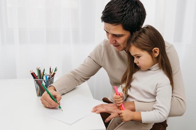 Vader speelt met kleurpotloden met dochter