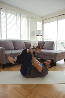 Vader speelt met zijn baby in de woonkamer