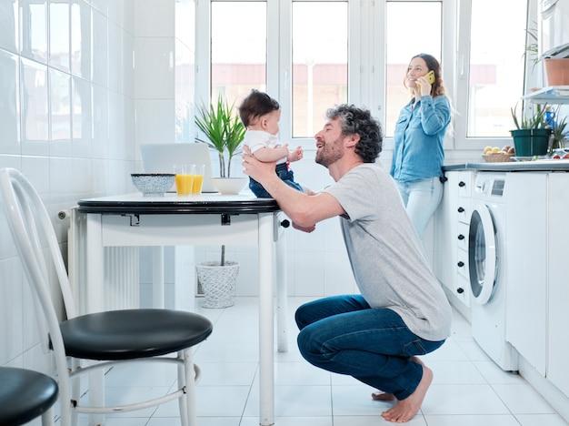 Vader speelt met zijn schattige babymeisje in de keuken terwijl de moeder vanuit huis werkt en een telefoontje beantwoordt