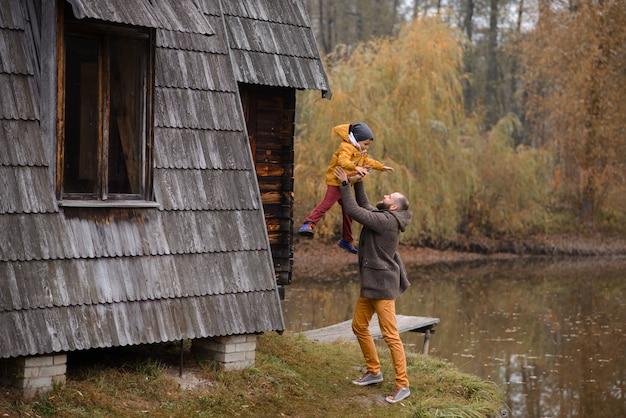 Vader speelt met zijn zoon en gooit hem overeind terwijl hij in het herfstbos loopt.