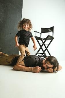 Vader spelen met jonge zoon in hun zitkamer thuis. jonge vader die plezier heeft met zijn kinderen in vakanties of weekend