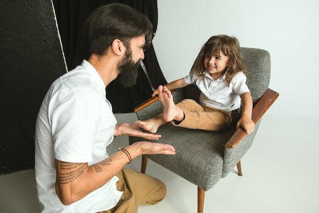 Vader spelen met jonge zoon in hun zitkamer thuis. jonge vader met plezier met zijn kinderen in vakanties of weekend. concept ouderschap, kinderjaren, vaderdag en familierelatie.